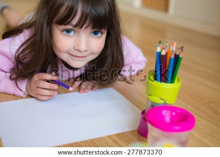 Baby girl with big cute blue eyes drawing - stock photo