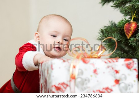baby girl with big gift box on christmas tree background