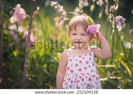 baby girl with blue eyes blond hair and pink peony in her hair in summer garden with bright flowers.  She dressed on white with floral pattern summer dress.  - stock photo
