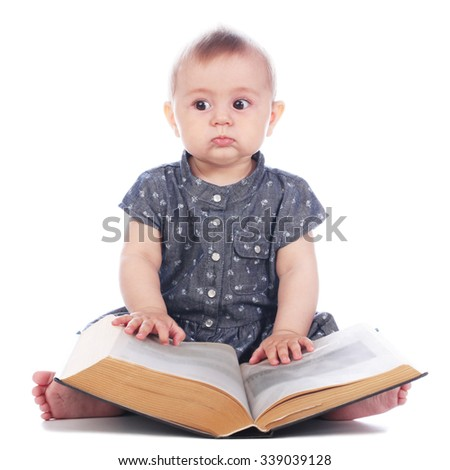 Baby girl with book sitting on white background - stock photo