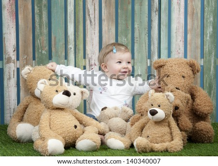 baby girl with group of teddy bears, seated in front of a fence