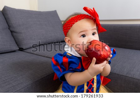 Baby girl with halloween party dressing and apple