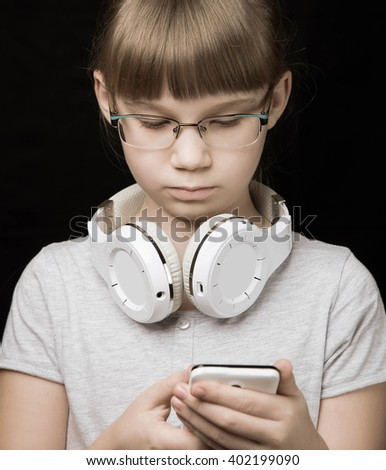 baby girl with headphones and phone on a dark background - stock photo