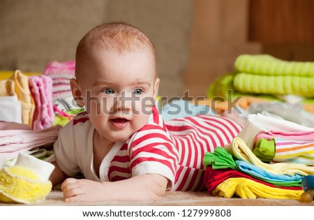 Baby girl with heap of baby's wear laying on checked blanket - stock photo