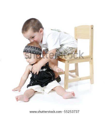 Baby girl with her brother kissing her on the head - stock photo