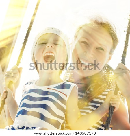 baby girl with her mom on a swing outside. - stock photo