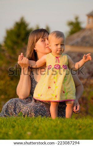 Baby girl with her mother in summer park in the evening