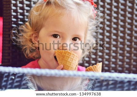 baby girl with ice cream sitting in cafe - stock photo