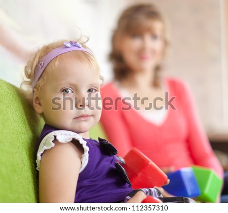 baby girl with mother in home interior - stock photo