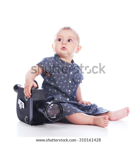 Baby girl with old retro movie camera sitting on white background