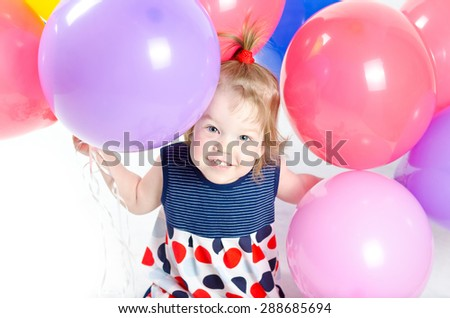 Baby girl with party balloons over white - stock photo
