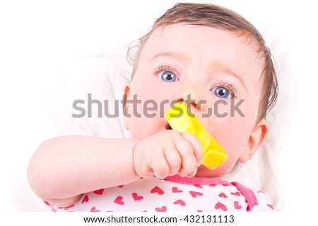 Baby girl with rattle teether toy.