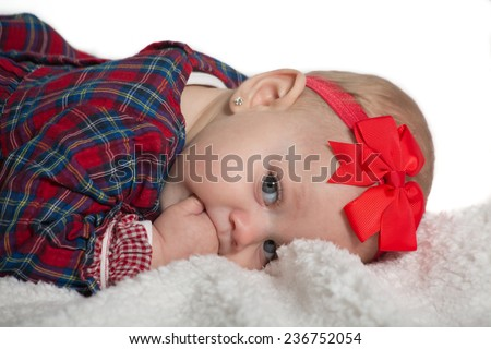 baby girl with red ribbon, laying on bed, put fingers in her mouth  - stock photo