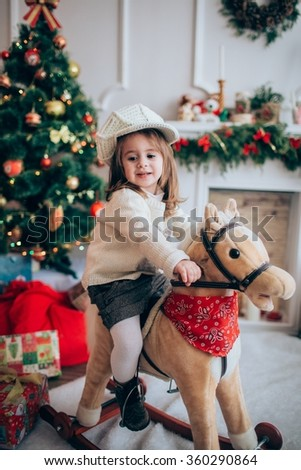 Baby girl with toy horse near Christmas tree - stock photo