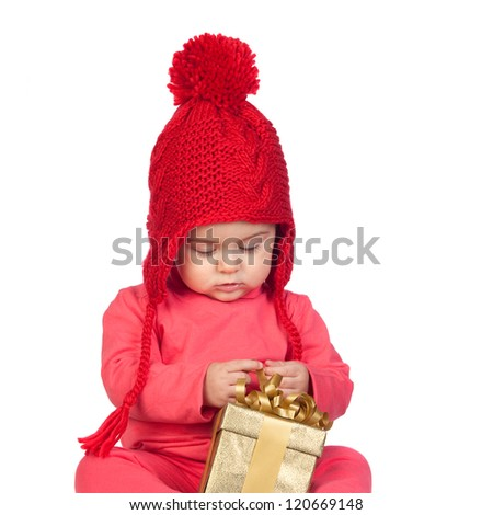 Baby girl with wool hat looking a gift isolated on white background - stock photo