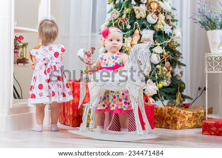 baby girls next to a horse rocking near a Christmas tree - stock photo