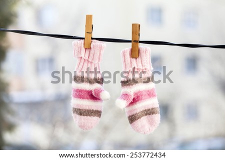 Baby gloves hanging on the clothesline. - stock photo