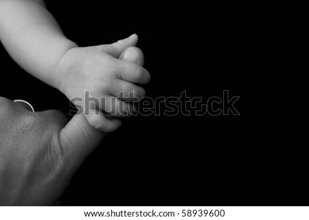 Baby grasping her fathers finger with room for copy