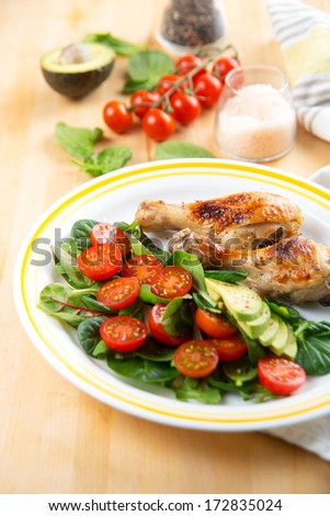Baby Greens and Tomato Salad Served with Chicken Drumsticks - stock photo