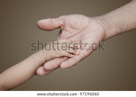 Baby hand and Adult hand touching each orther - stock photo