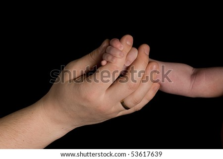 Baby hand and Father hand on black background