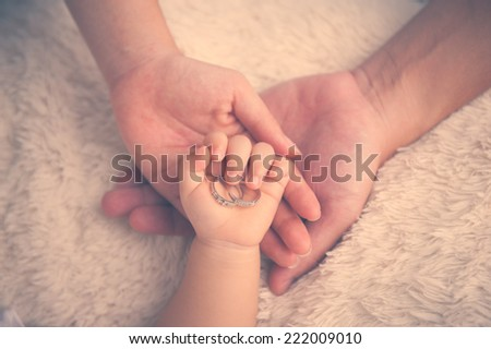 Baby hand. Closeup of baby hand into parents hands. Family concept with the wedding rings on baby hand. - stock photo
