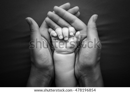Baby hand holding in mother hands isolated in grey background, happy family hands, newborn life