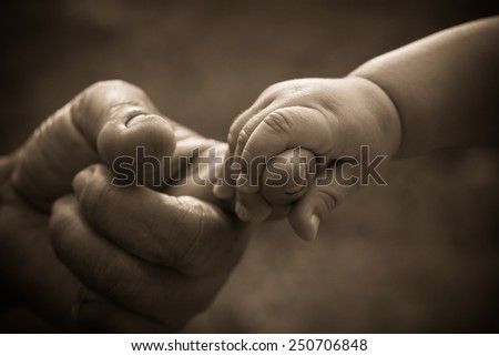 Baby hand holding mother finger with retro effect - stock photo