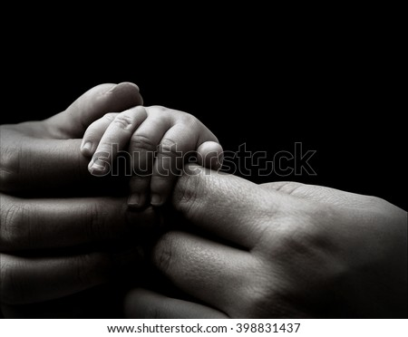 Baby hand holding mother's hands, isolated on black