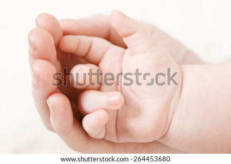 Baby hand in mother hand, close-up