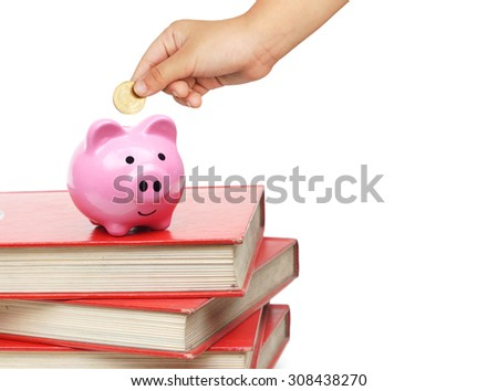 baby hand putting golden coins into a pink piggy bank on books  - saving money for education concept - stock photo