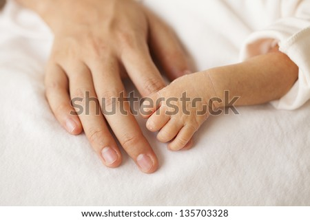 Baby hands and the hands of his mother. - stock photo