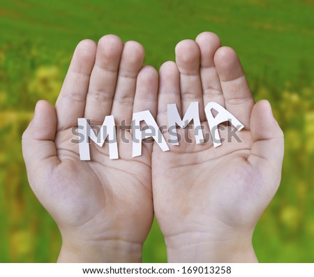 Baby hands holding carved the word mother on the background of a summer meadow - stock photo