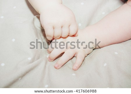 Baby hands on cosy textile. - stock photo
