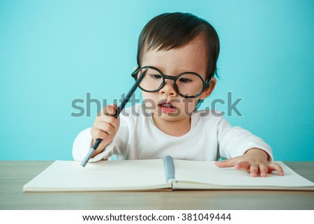 Baby happy wearing glasses on the table, new family and love concept (soft focus on the eyes) - stock photo