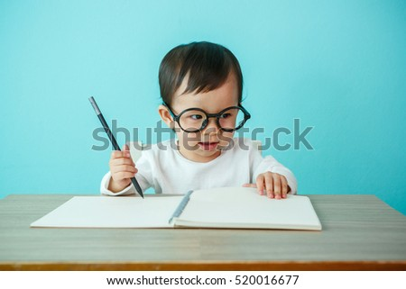 Baby happy wearing glasses on the table, new family and love concept (soft focus on the eyes)