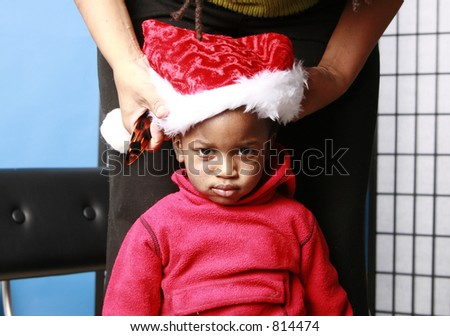 Baby having a santa hat put on - stock photo