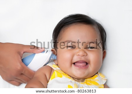 Baby having temperature taken using an infrared ear thermometer - stock photo