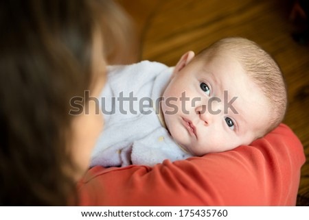 Baby held in mother's arms for comfort - stock photo