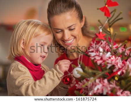 Baby helping mother decorate christmas tree - stock photo