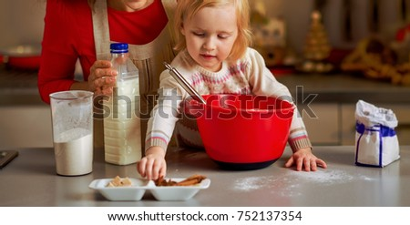 Baby helping mother make christmas cookies in christmas decorated kitchen
