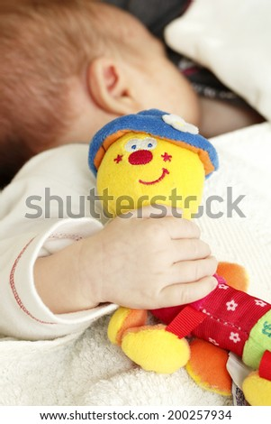 Baby holding a toy - stock photo