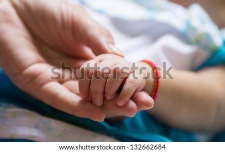 Baby holding adult finger
