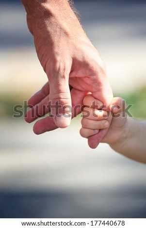 baby holding dad's finger