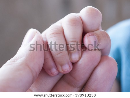 Baby holding father's hand ,family love and relationship - stock photo