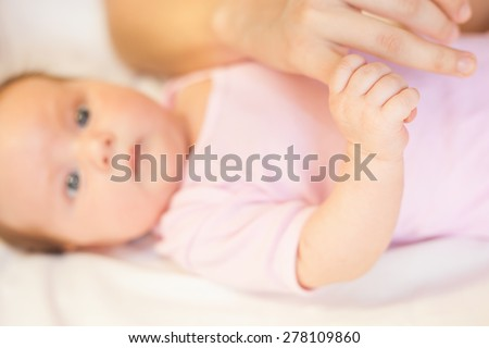 Baby holding mother finger, there is concept or idea of care, family and happiness at the home, like mother caring for newborn
