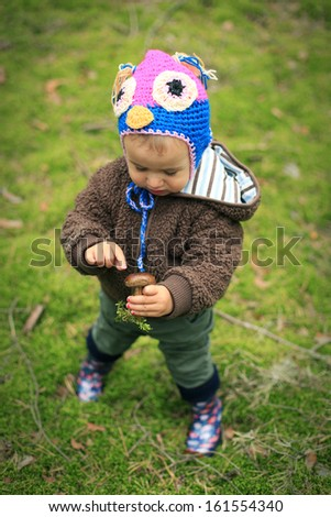 Baby holding mushroom in the forest - stock photo