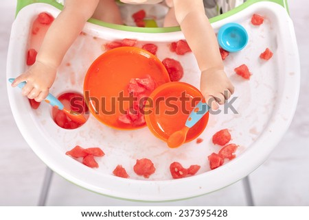 Baby holding spoon and fork and making mess on table - stock photo