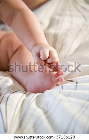 Baby holding toes in his chubby fist - stock photo