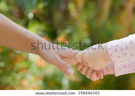 Baby holds mothers hands outdoors, selective focus